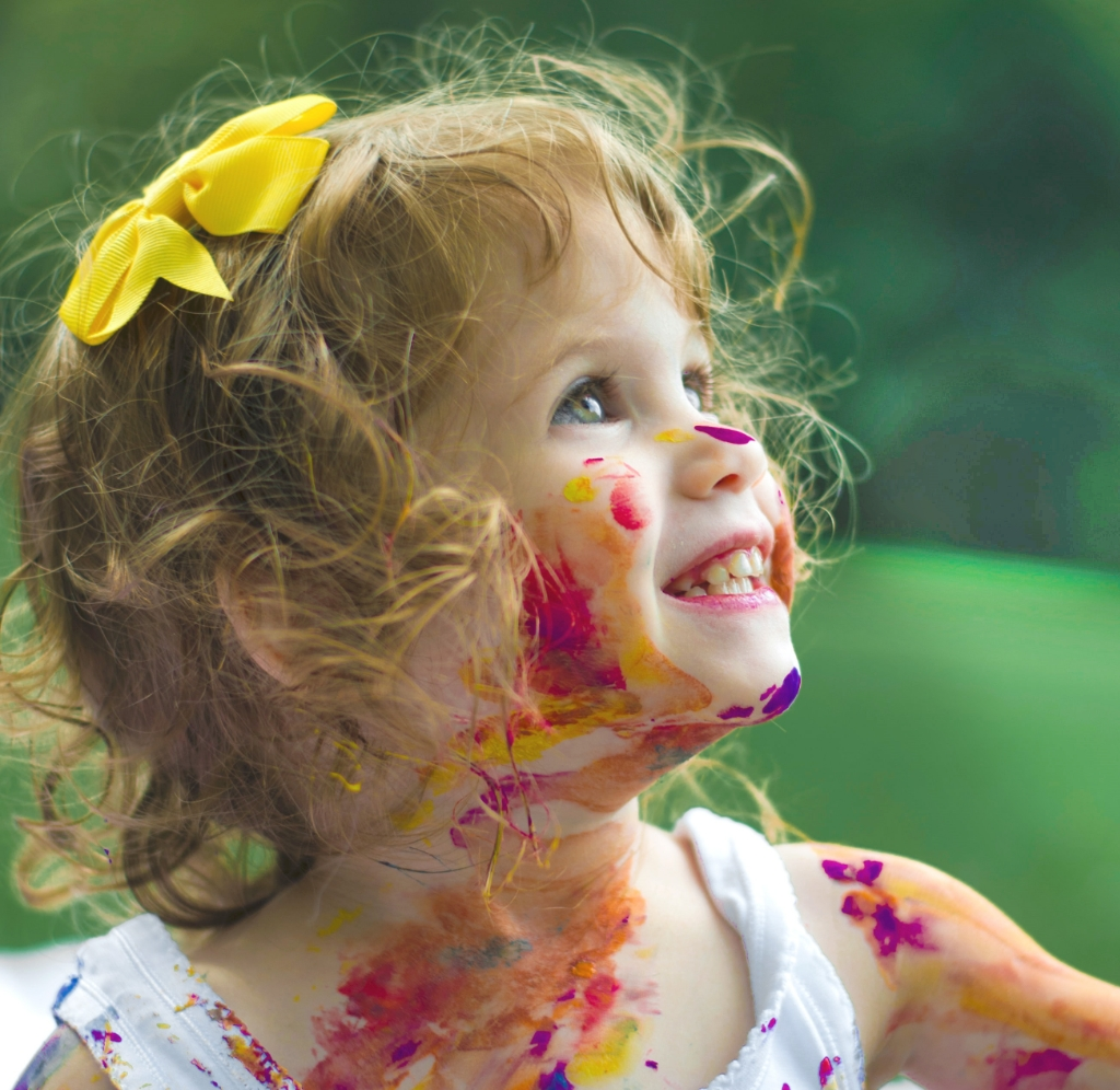 happy girl covered in paint with yellow bow